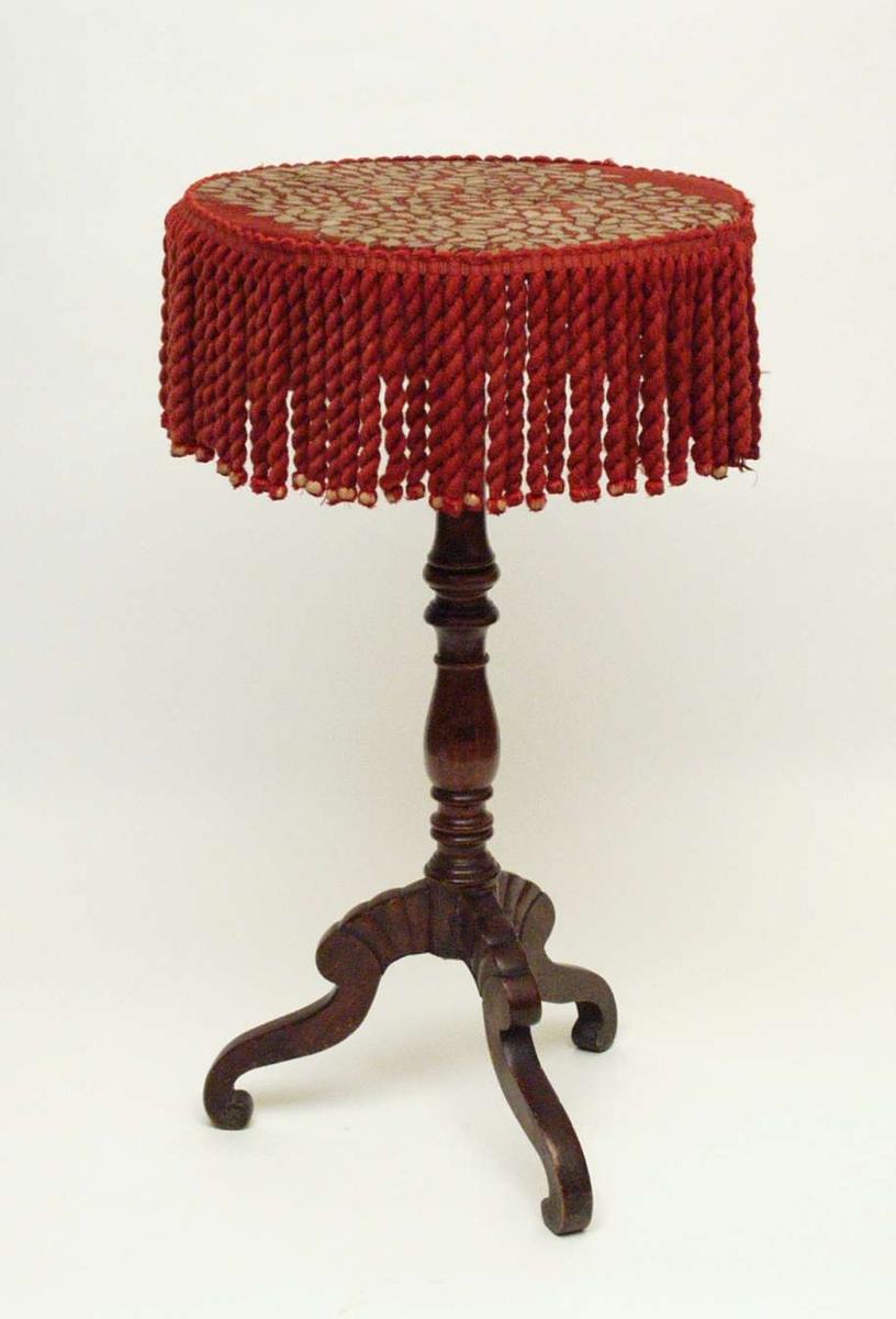 Rundt lite bord dekket med stolenes møbelstoff og kantet med atten cm. lange frynser. Trinn profilert søyle med tre utsvugne ben.