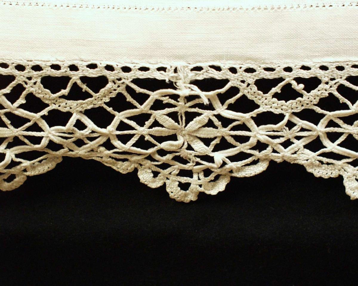 Linduk (maskinvevd 20x22 tr/cm) med bomullsblonder på tre sider.  2-2,4 cm brett med stikkhullfald på kortsidene og ene langsiden, hvor blonde er påsydd med kastesting. Jare i andre langsiden.