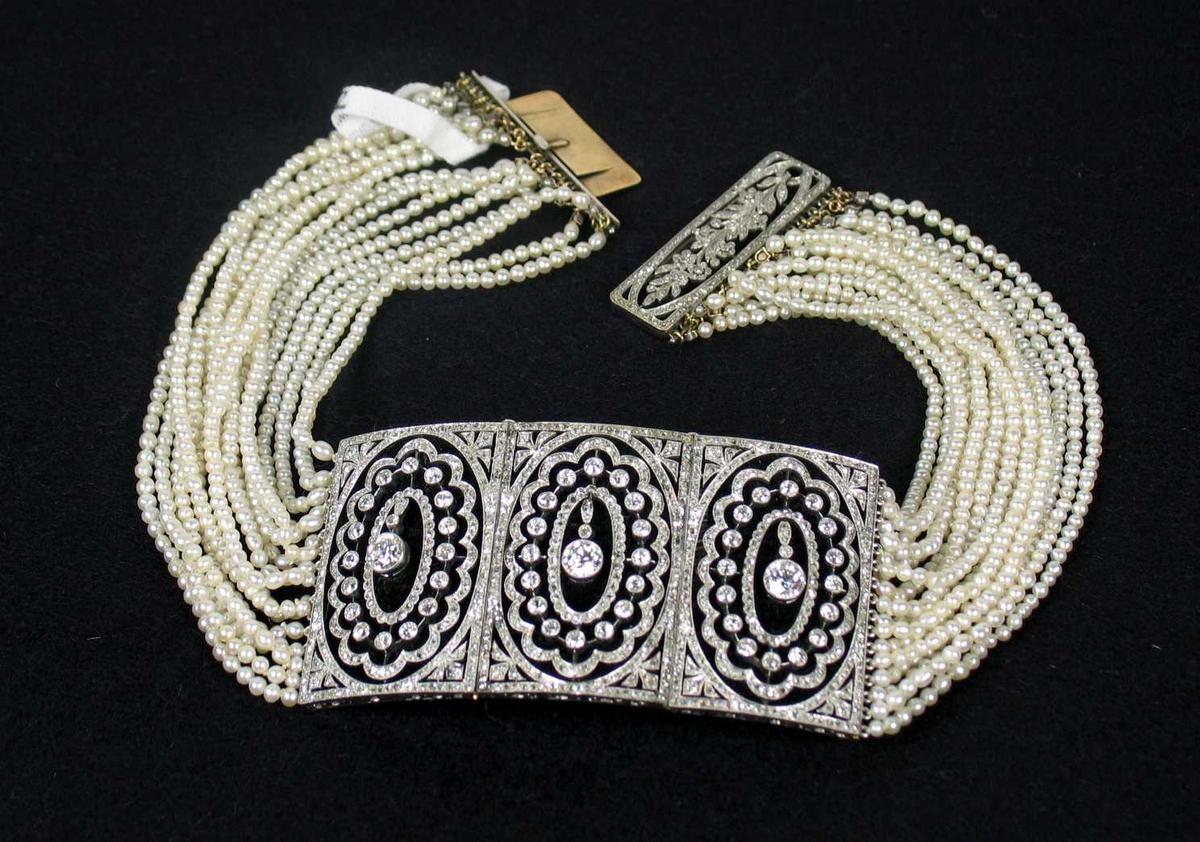 Halssmykke med et tredelt felt foran av hvitt gull og diamanter. Kjedet er satt sammen av seksten perlerader med ulik lengde. Låsen er dekorert med en kvist innfattet steiner.  Smykket ligger i originalt etui.