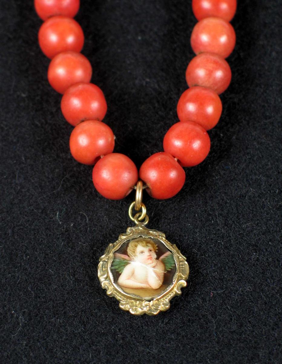 Rødt kort perlekjede med medaljong. Den har flerfarget trykt (?) englemotiv og blomsterdekor langs kanten og på baksiden. Medaljongen kan åpnes.