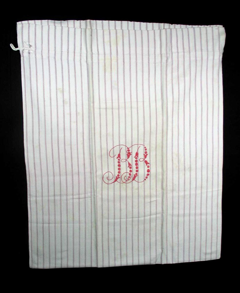 Skittentøypose i smalstripet bomullstoff med BB's monogram i rødt. Tøyet er lagt dobbelt, bukt i bunnen og sydd sammen i sidene jare mot jare. Nedbrett øverst med løpegang og snor. Monogrammet er brodert med kontursting og plattsøm.