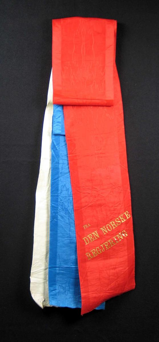 Begravelsessløyfe i rød, hvit og blå silke med tekst i gull.