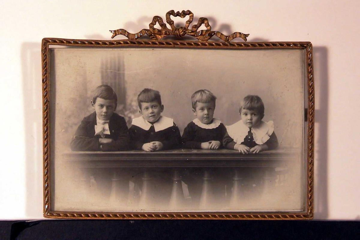Gruppeportrettt. Fire gutter bak ballustrade-arrangement. Alle i svarte dresser, de yngste med løse, hvite krager, den eldste med hvit sløfe. Alle lener seg mot gelenderet i fotoatelieet.