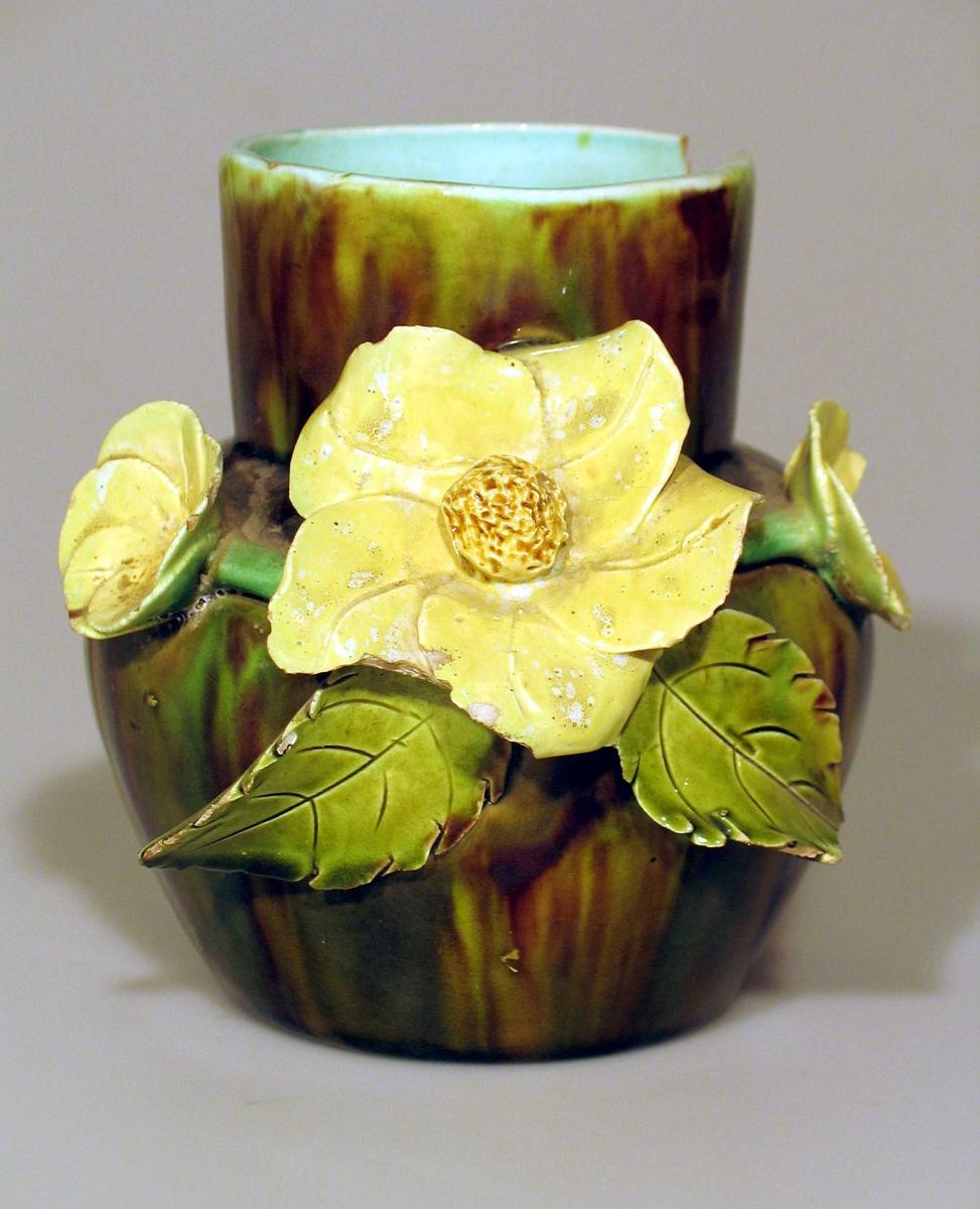Vase i steintøy med grønlig glasur i mørk chang-chang utvendig. Innvendig turkis. Dekorert med blomster og blad i relieff.