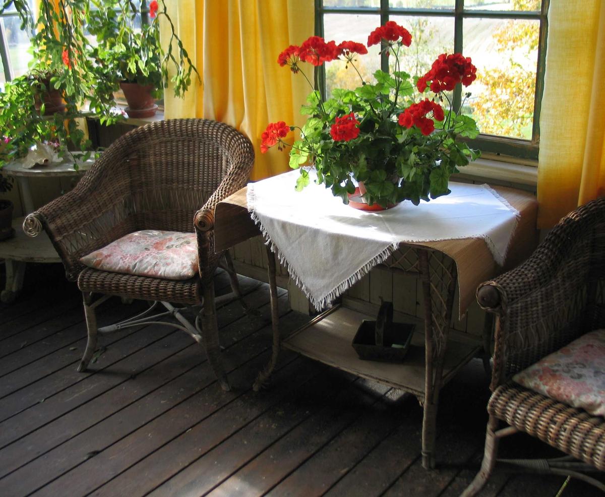 Kurvbord med brutte hjørner og stråvevd plate og hylle. Sarg og bein er i pil og har rutemønster. Bordet har en løper i strå.