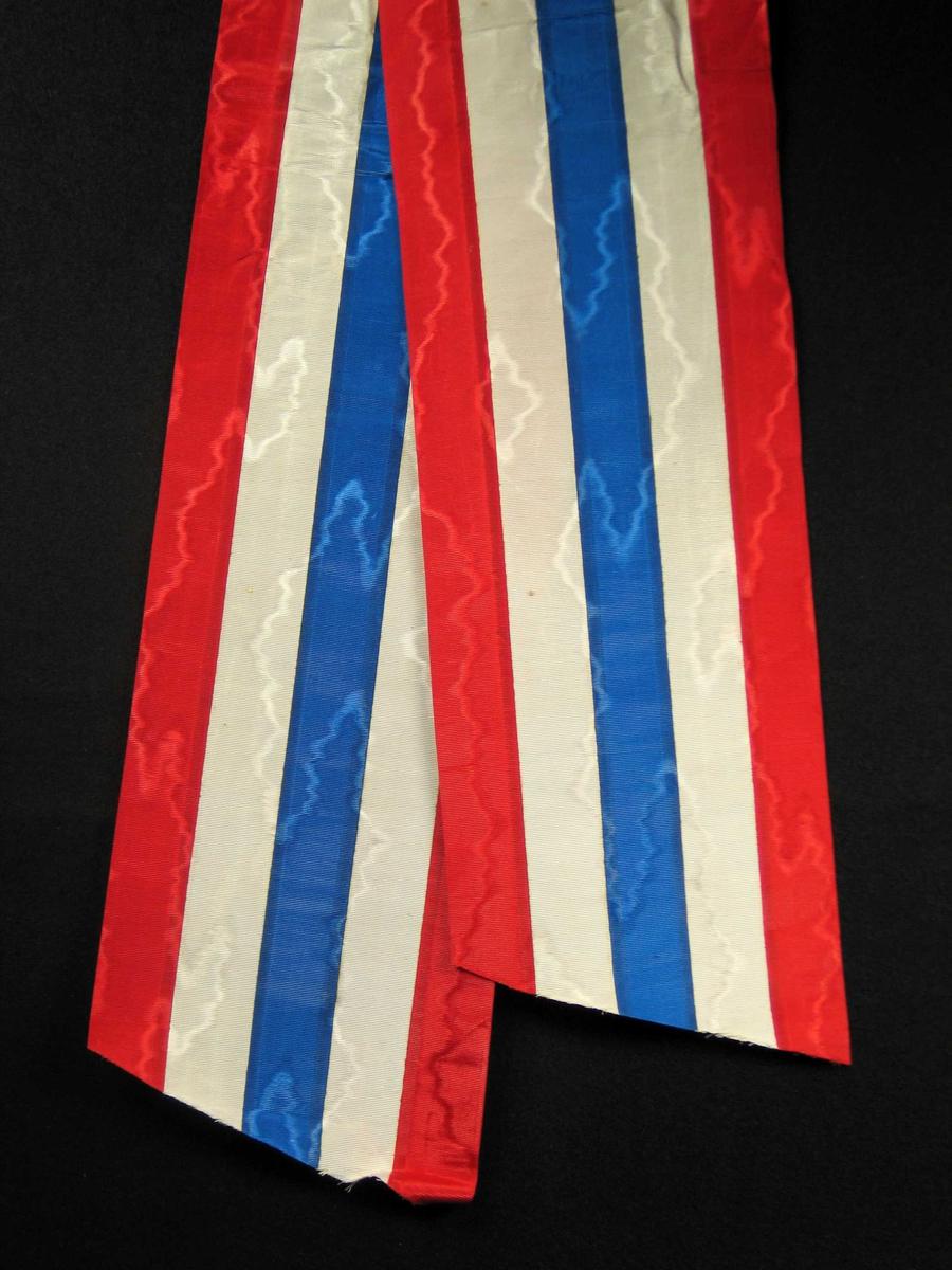 Begravelsessløyfe i rød, hvit og blå silke uten tekst.