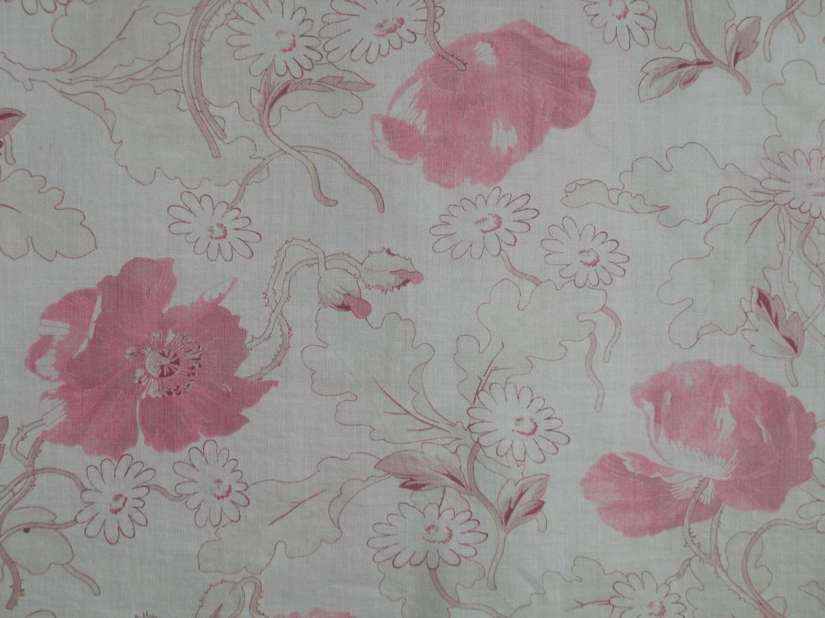 Forheng i trykt bomullstøy med rosa blomsterdekor. Det er sydd sammen av to deler, jarer i sidene. Påsydde bånd for oppheng.