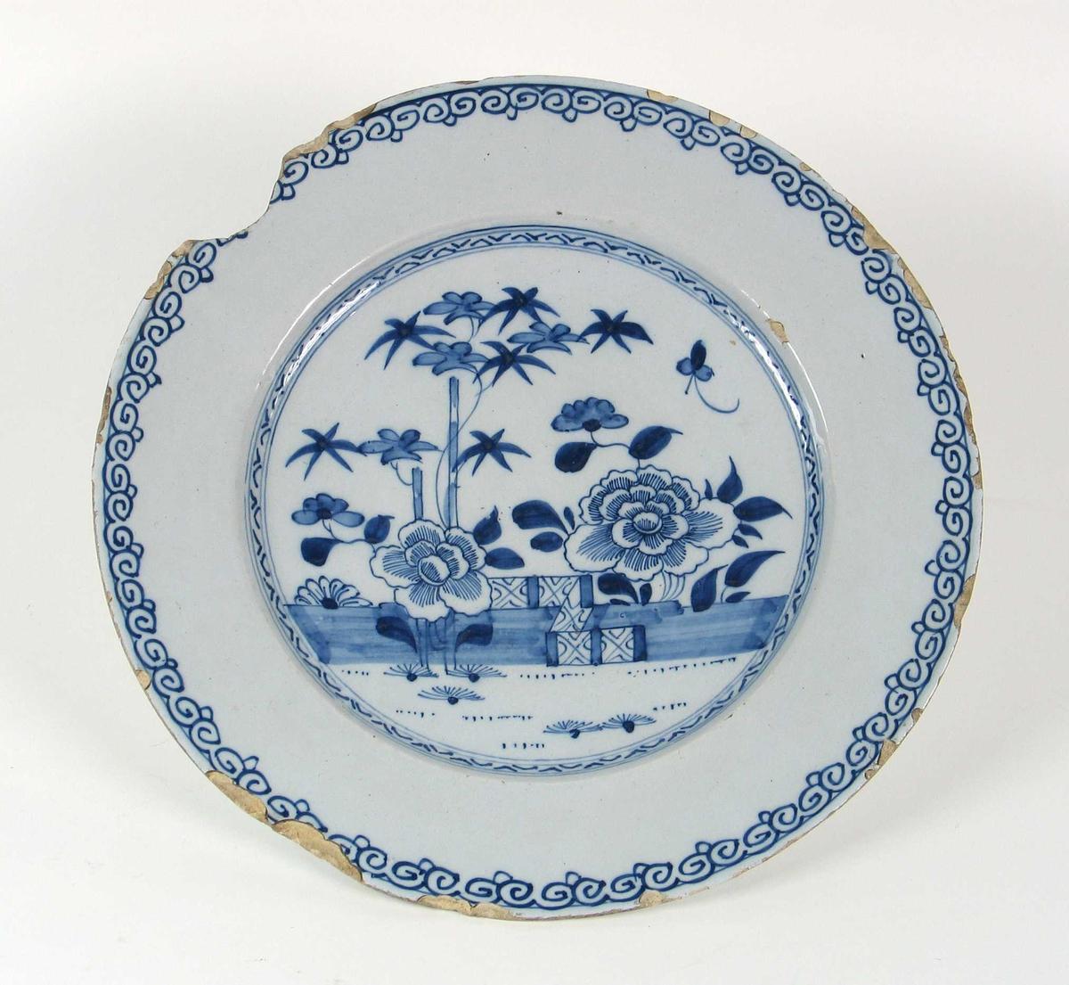 Blåmalte vegetabilske motiver og et gjerde i bakgrunnen, to store blomstermotiver i forgrunnen. Smal bord langs bunnen, bredere ved kanten.
