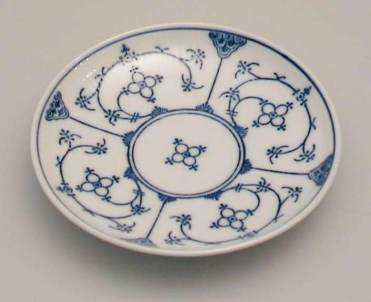 Kaffeskål  i porselen med riflet gods og blått mønster. Stempelet har to piler i kors.