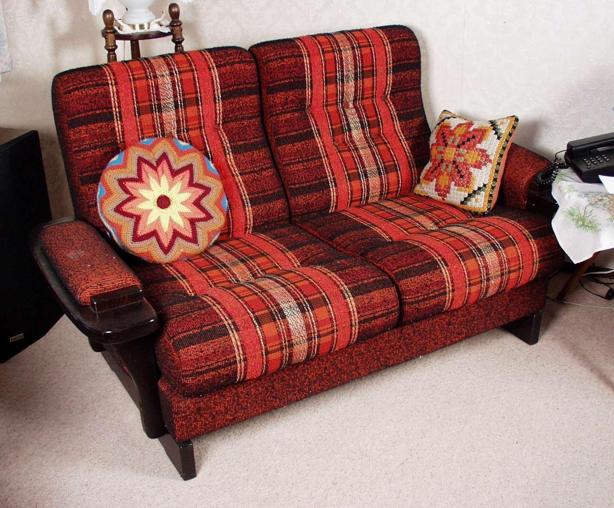 Sofa trukket i brunsvart stoff med rustrød og oransje felt. Treverket er i beiset bøk. Vendbare seteputer.
