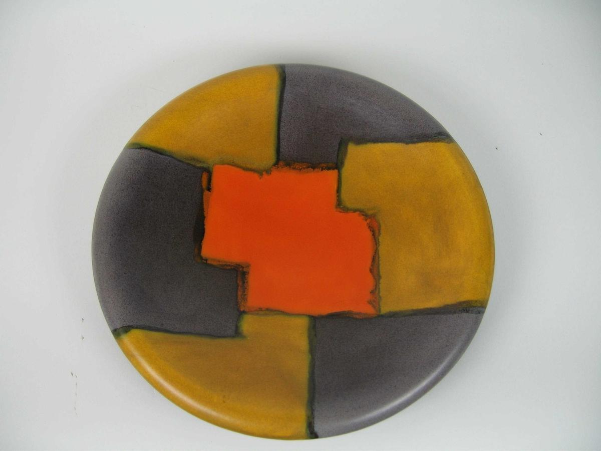 Rundt keramikkfat. Fatet har nedbrettede kanter. Undersida er svartglasert, oversida er dekorert med felter i orange, gulbrunt og gråbrunt med utflytende svart konturstrek.