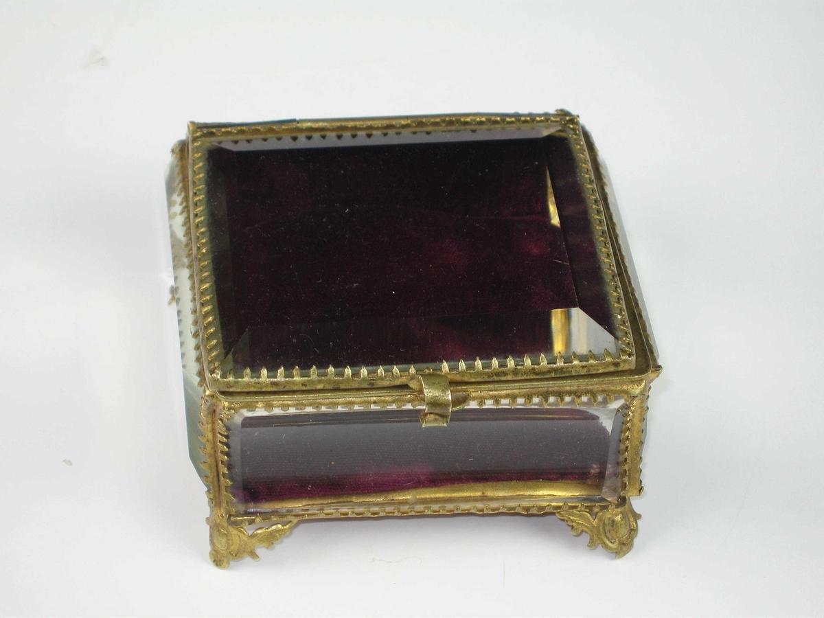 Skrin av slepet glass satt inn i et rammeverk av messingfarget metall. Skrinet er formet som en bok, og det står på fire lave bein. Lokket er hengslet. Inne i skrinet en burgunderrød fløyelspute,