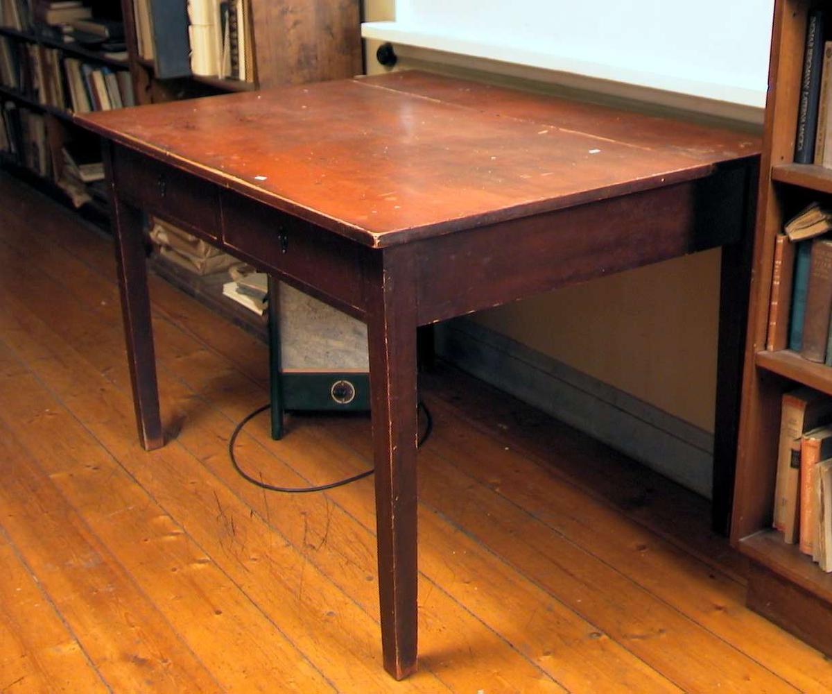 Bord med to skuffer. Bordet er malt rødbrunt, men malingen er avslitt. Bordplaten er flekkete og sprukket. Skuffene har beslag.