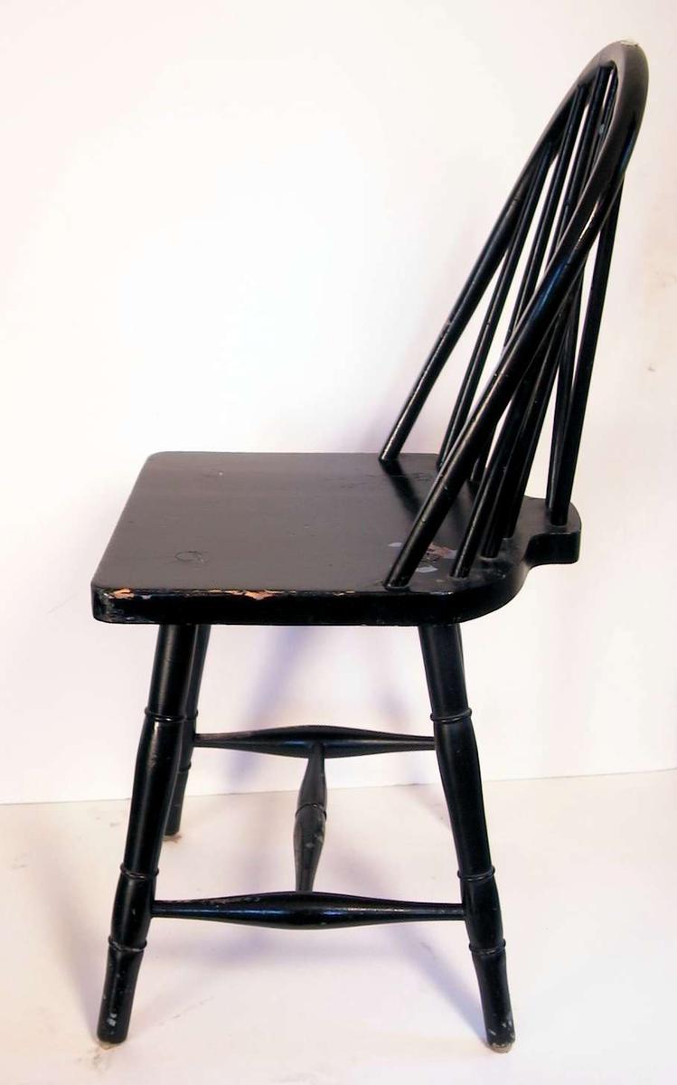 Sortmalt pinnestol med sprosser i ryggen. Malingen er avslitt.