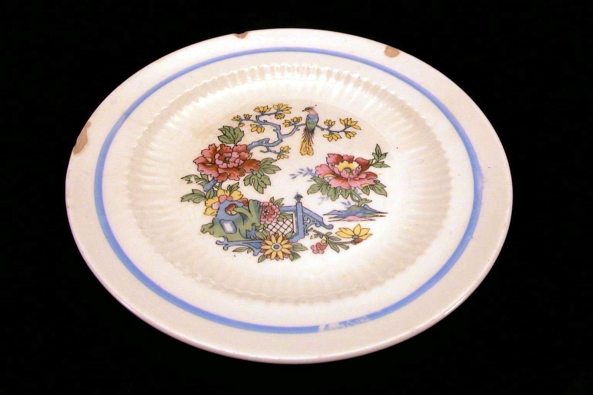 Asjett med hvit glasur og østen-inspirert dekor i blått, rødt, gult, grønt. Det er skår i kanten.