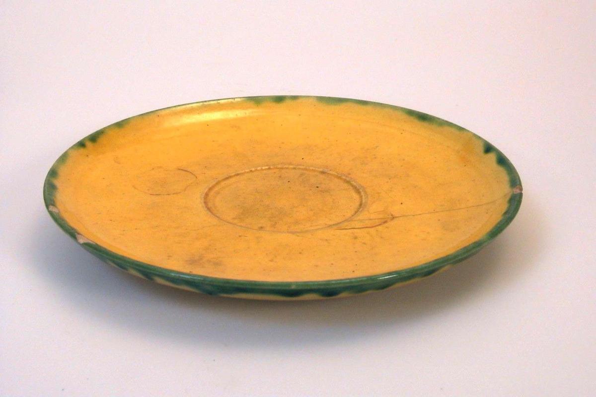 Skål i gul keramikk med grønn dekor. Brukskunst.
