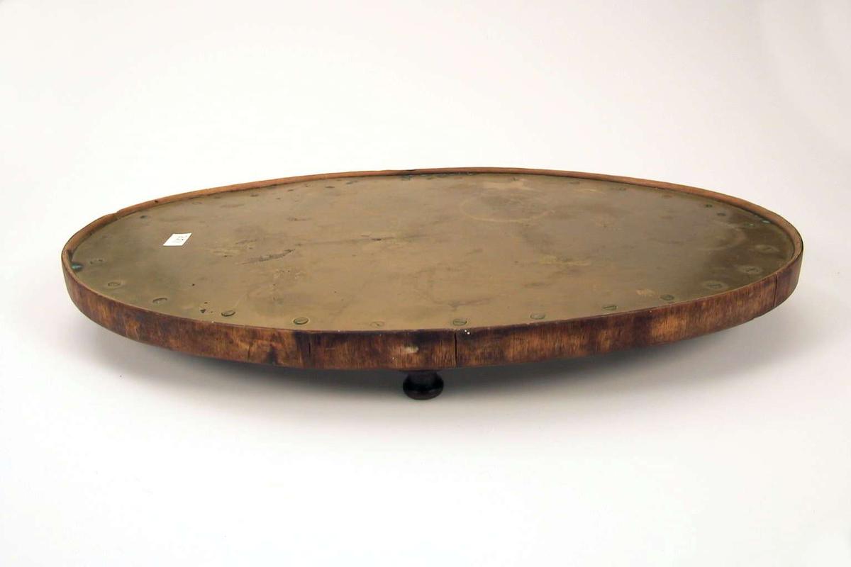 Oval bordskåner i tre med messingplate. Den har fire dreide føtter. Messingplaten er festet med messingskruer.