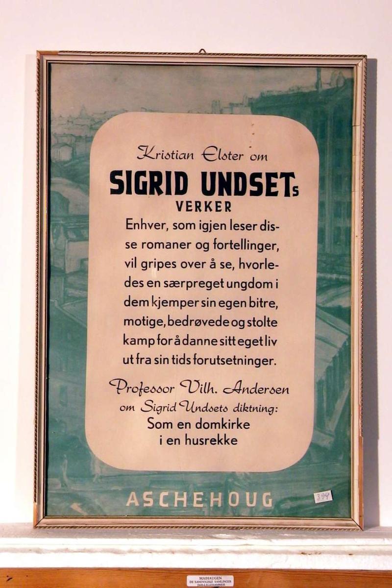 En innrammet plakat som reklamerer for S.U.s verker. Rammen er hvit med forgylling.