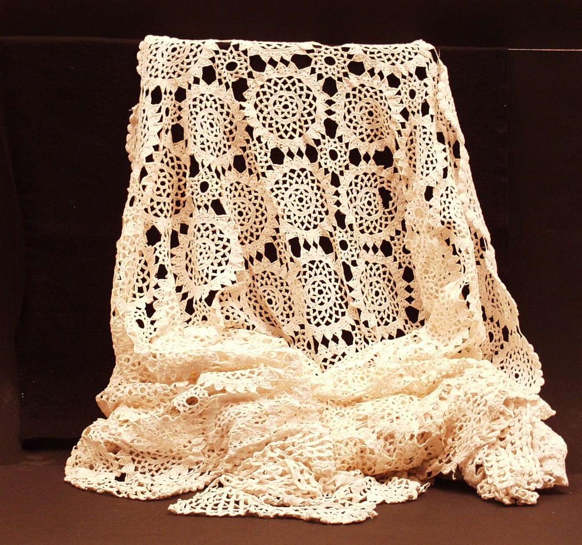 Heklet, hvitt sengeteppe til dobbeltseng. DMC-garn (bomull merc.). Sammensatt av sirkler og kantet med spisser/trekanter på tre kanter.