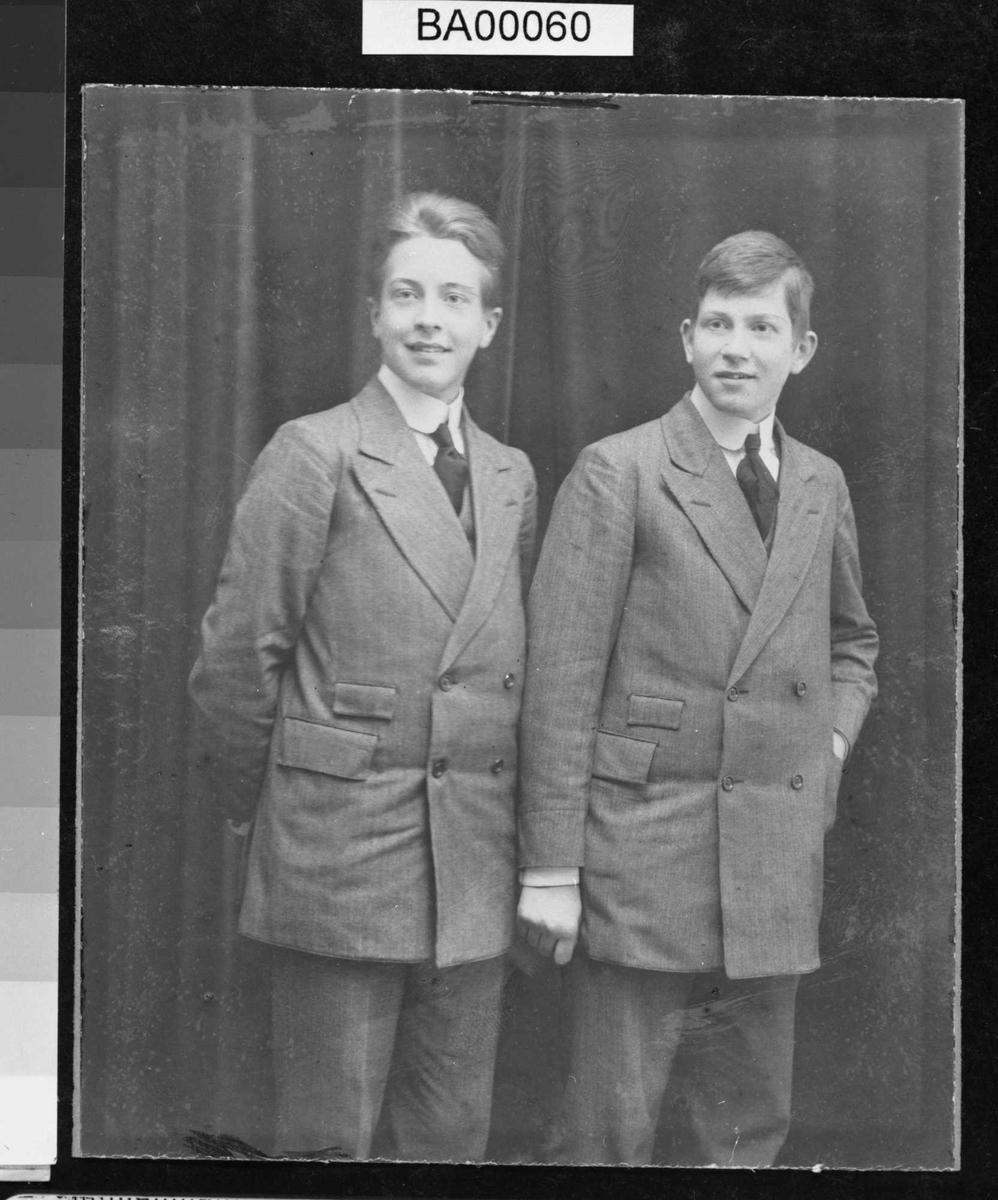 Fotografi av to unge menn i stripet dress.