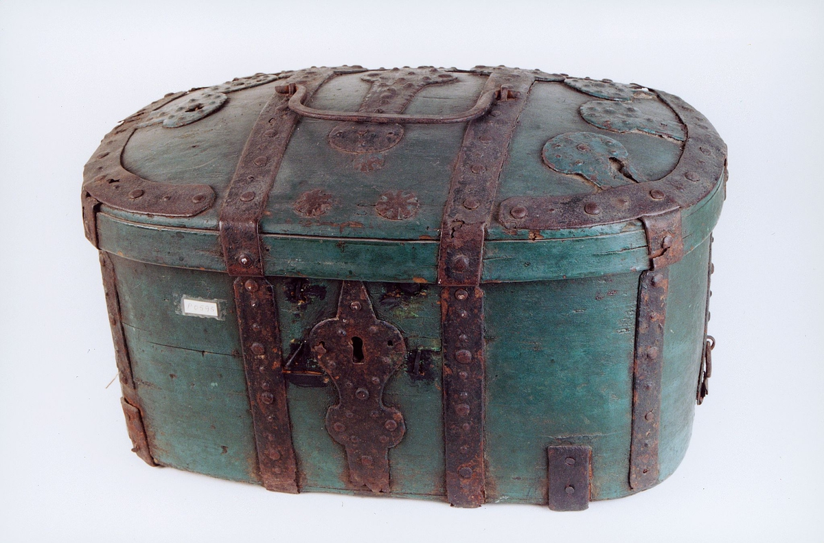 Grønn bærbar transportkiste i tre med jernbeslag og bærehåndtak i lokket og låsbeslag i jern.