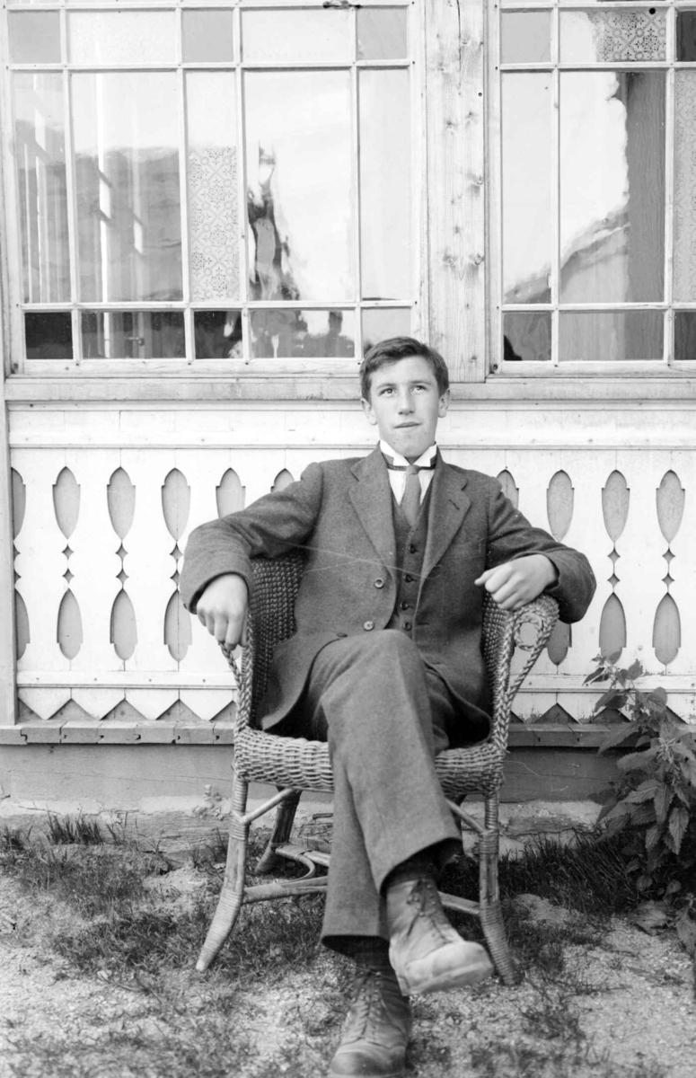 Portrett av en ung mann sittende i stol foran glass veranda