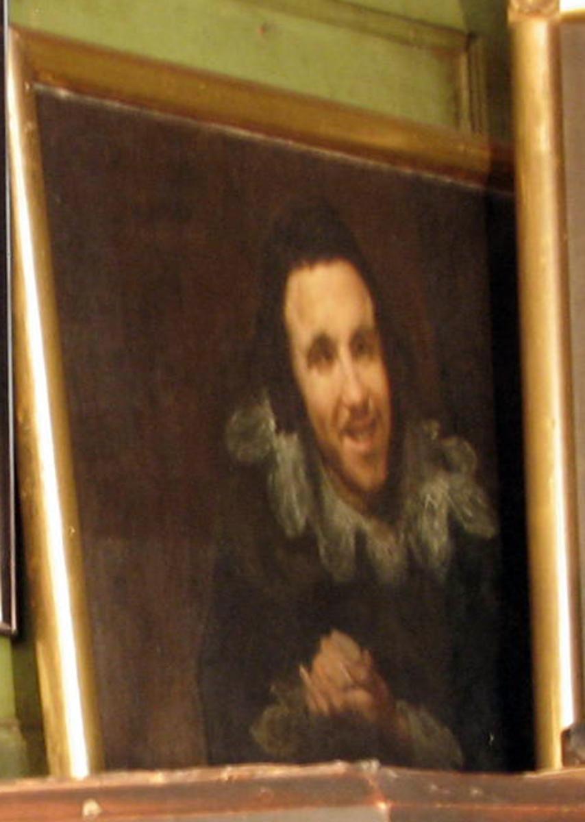 Rektangulært. Portrett mann, halvfig., ansikt noe høyrev., leende, brun karnasjon, sort drakt m. kniplinger, brun bakgr.