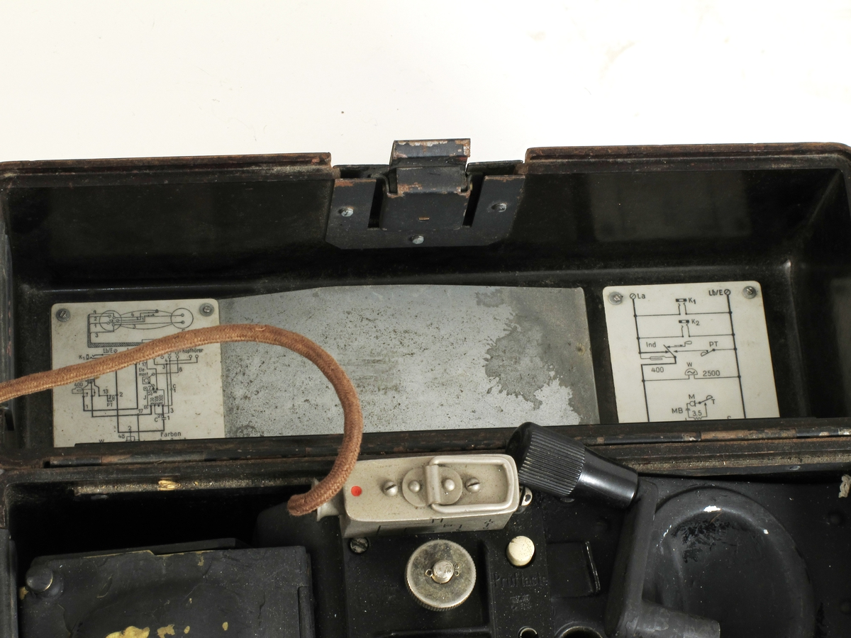Kasse med hengslet lokk, alt i bakelitt. Under lokket er telefonrør med ledning. Liste med kodeord for staving på lokket. I lokket er montert koplingsskjema.