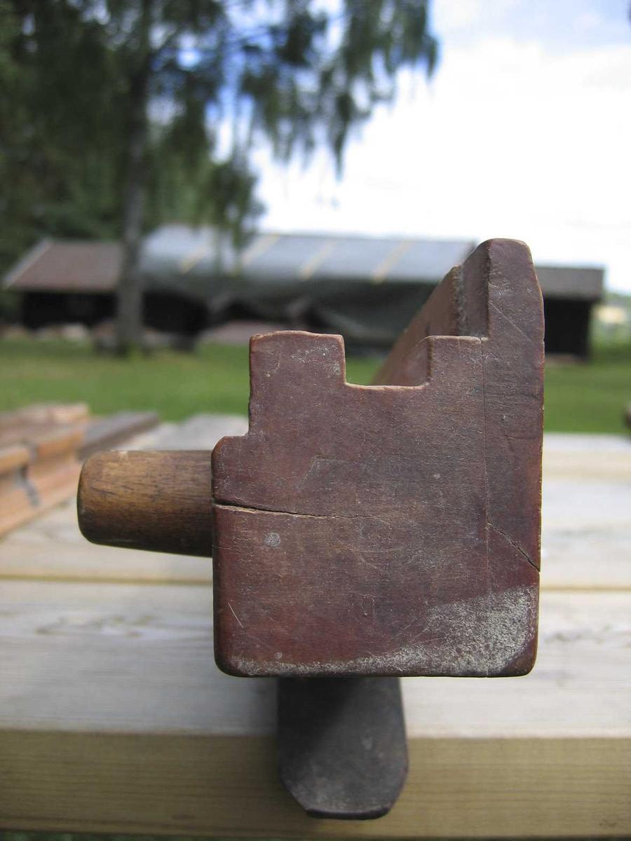 Kant + not som fjæra kan løpe i. Avstanden til kant er justert med påspikret flis. Kraftig knott til håndtak framme på høyre side.