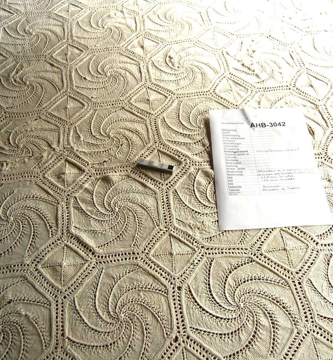 Strikket og heklet sengeteppe. Strikkede åttekanter og kvadrater føyd sammen med hekling.  Slitte partier er reparert med søm.