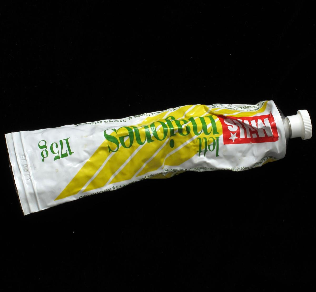 Majonestube, av metall, skrukork av plast. Dekor av gule striper på skrå, vareopplysninger og strekkode.
