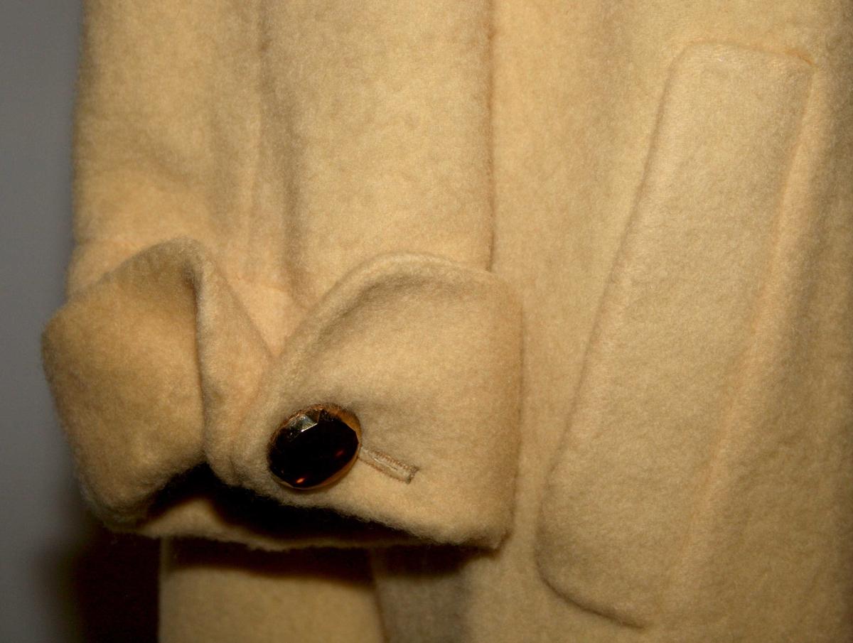 Swagger-fasong, buede skuldre, stor og rund nedslagkrage, 4 knapper foran, lomme ved hver hofte. Oppbrettet mansjett med knapp.