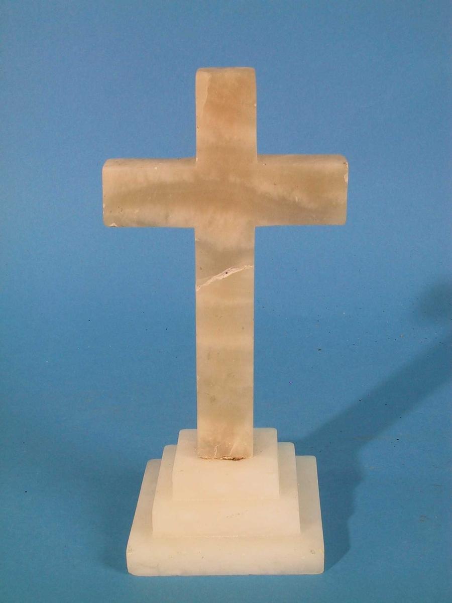 Kors i alabast. Kors på et postament med tre avtrapninger, firkantet. Tilstand: limt like under korsmidten, brudd på skrå.