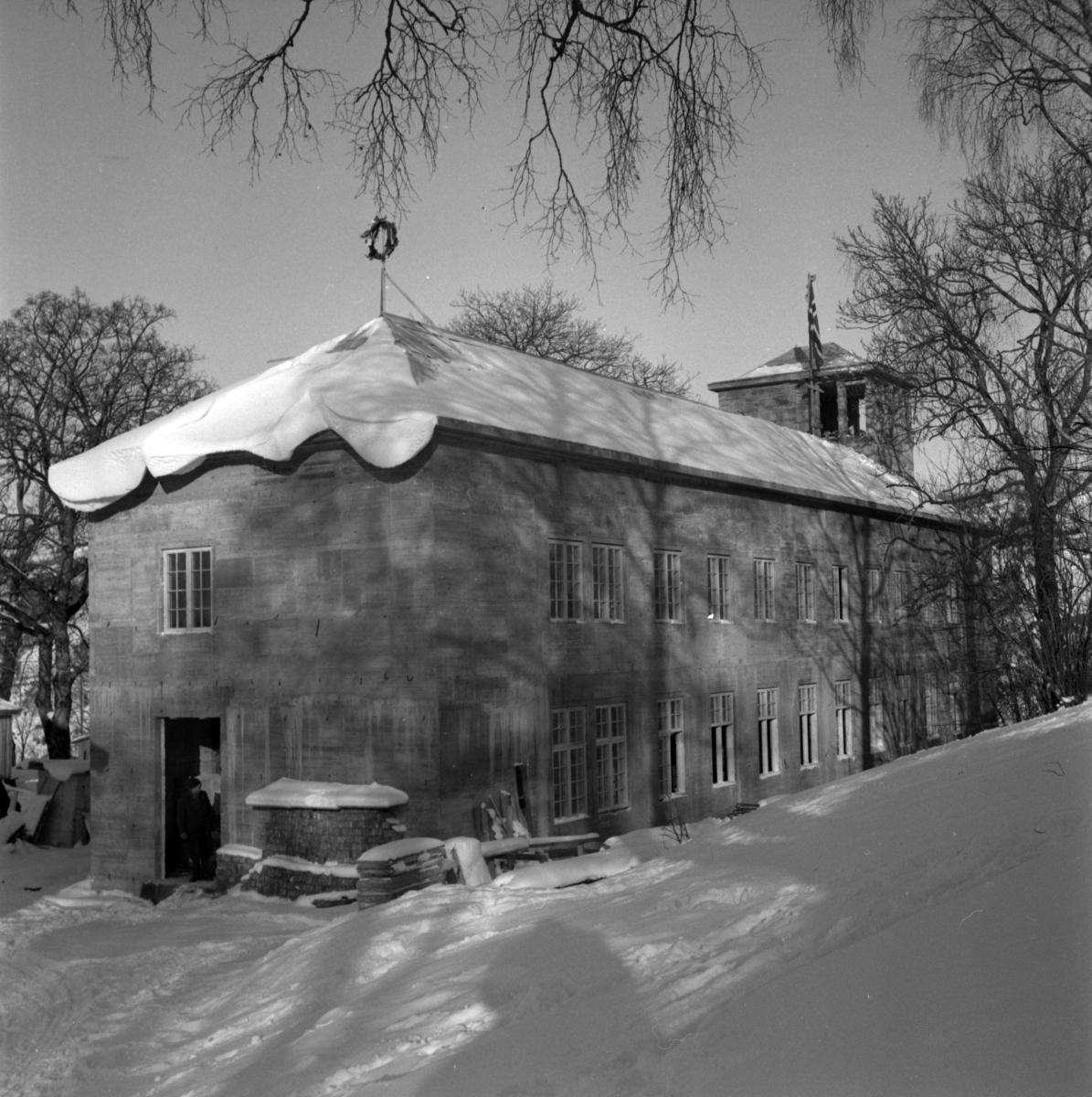 Aust-Agder-Museets første byggetrinn  - senere arkivfløy -  på Langsæ.  Kranselag. Vinter med snøl. Mennesker i døråpningen.