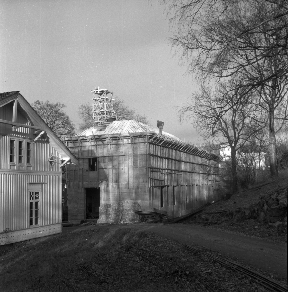 Aust-Agder-Museets første byggetrinn  - senere arkivfløy -  på Langsæ. Under oppføring. Gesims og takarbeid pågår. Mann på taket.