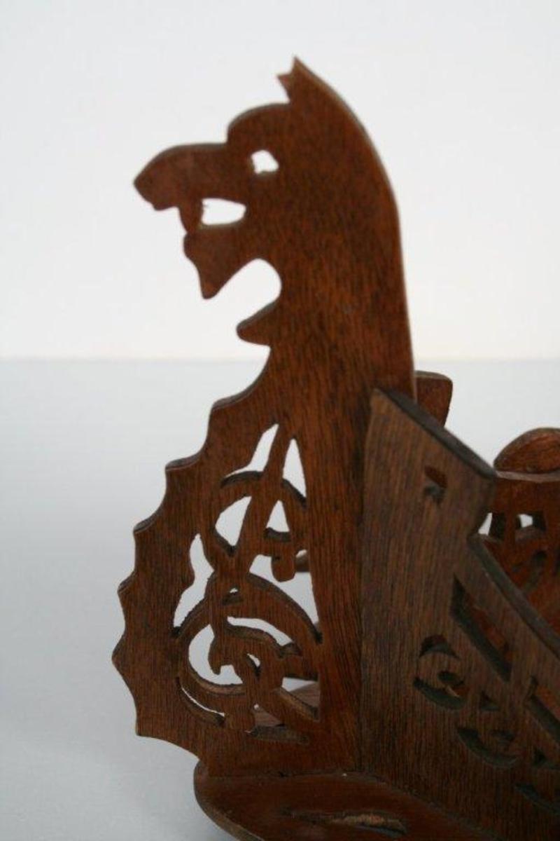 "Skål utformet som et vikingskip. Dragehode og ""urnesmotiv"" i hver stavn. Gjennomsagede motiver. En liten delfin i hvert hjørne."