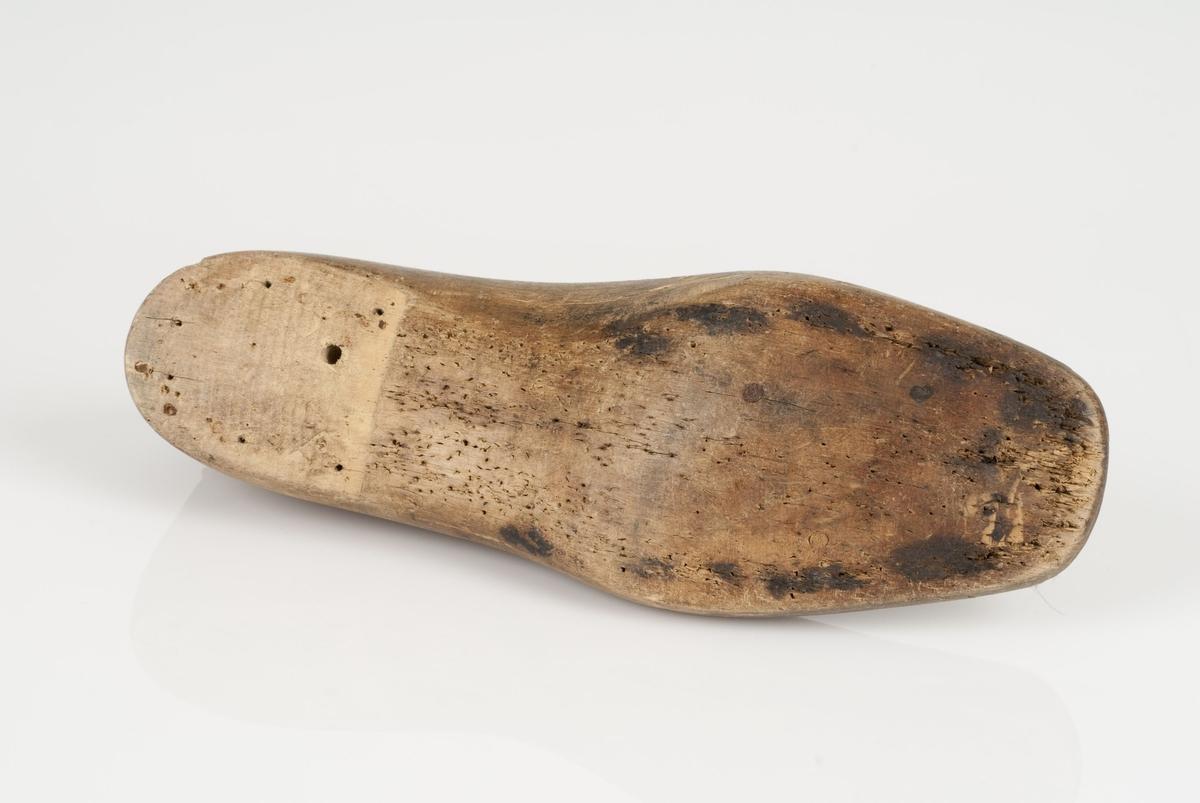 En tremodell i to deler; lest og opplest/overlest (kile). Venstrefot i skostørrelse 40, og 8 cm i vidde.
