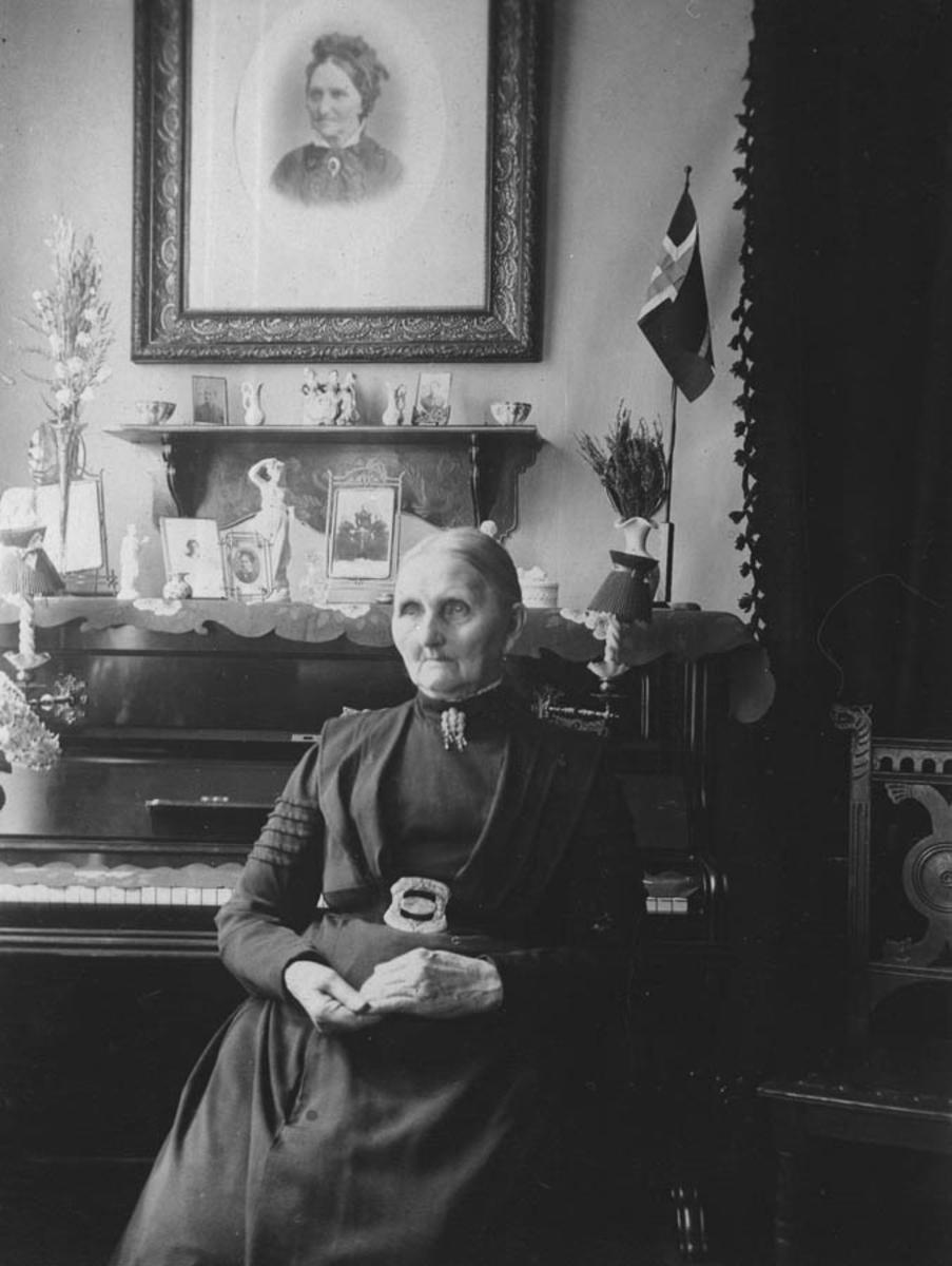 Elder kvinne foran et piano mrd gjenstander, bilder og nips.
