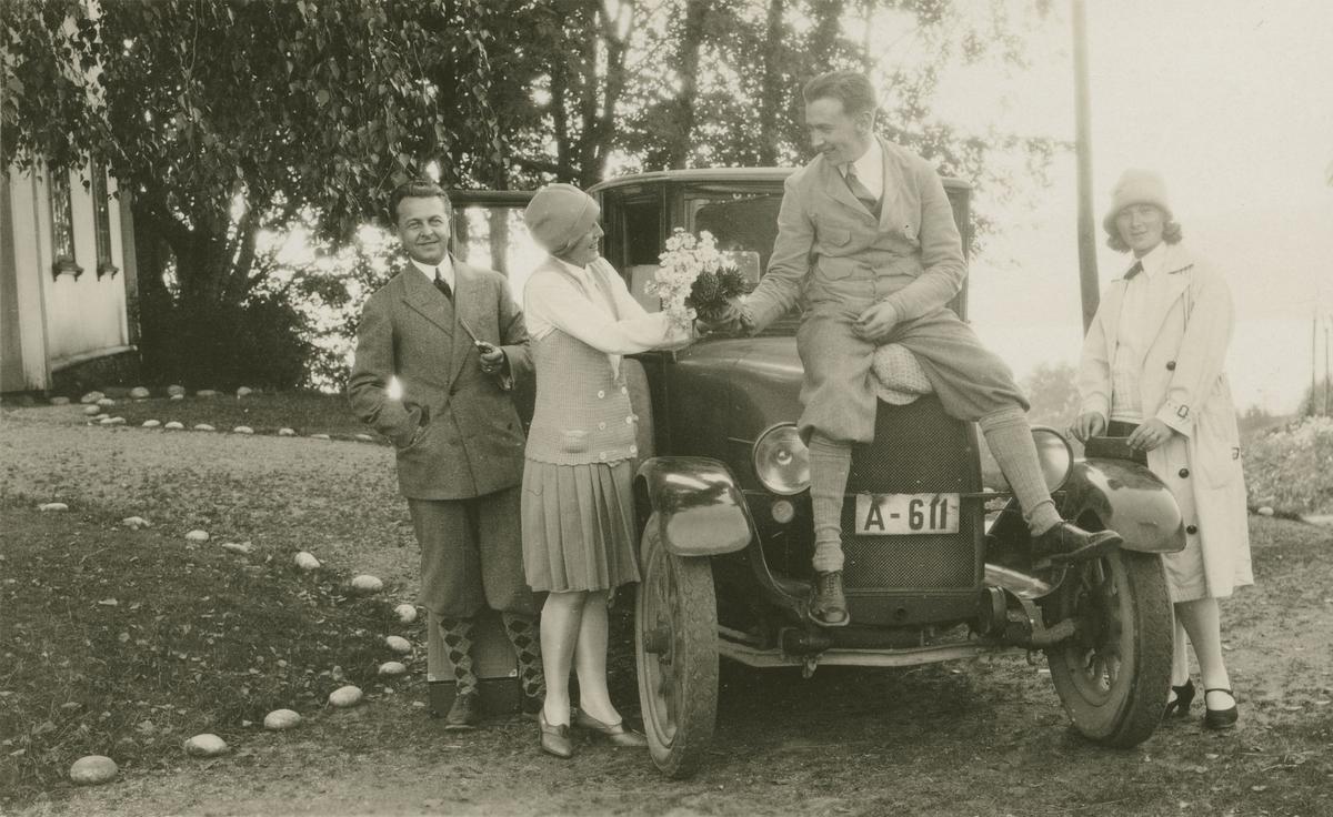To menn og to damer ved bil på gårdstun.