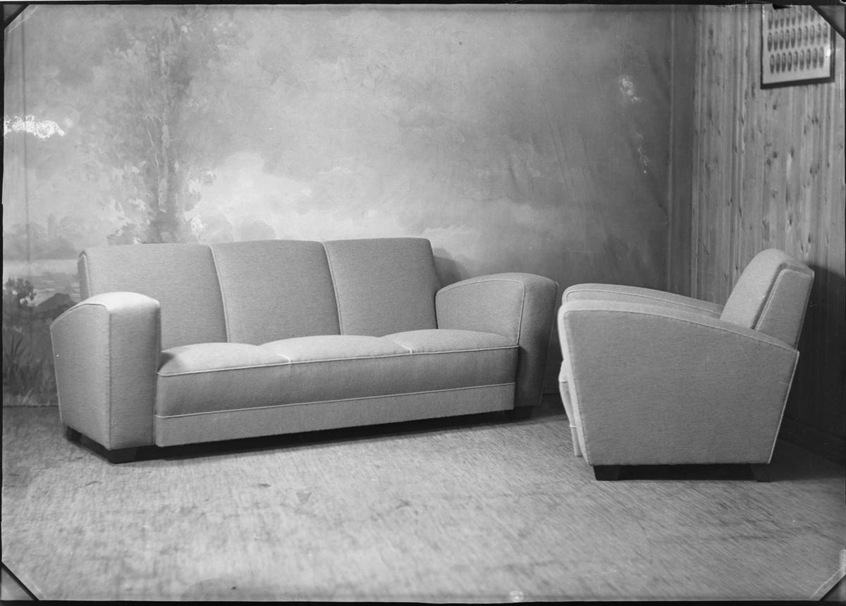 Studio opptak av en stol og en sofa.