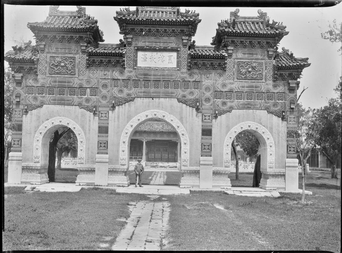 En turist under et steinmonument/portal med søyler og buede innganger. Trolig ved Sommerpalasset i Beijing.
