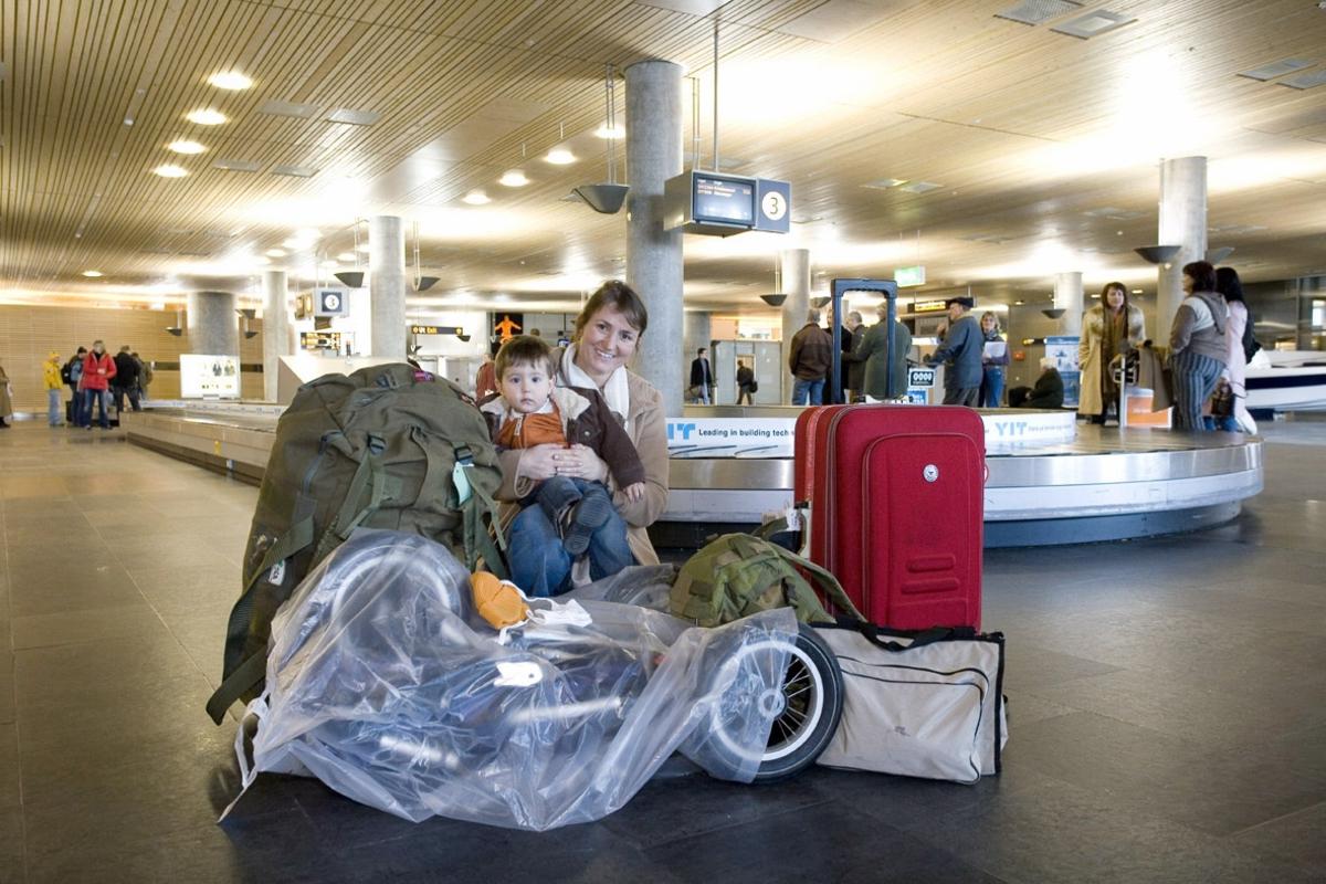 Vesker. Bagasjeutlevering innland. Mor med lite barn og bagasje, deriblant en barnevogn. Fotodokumentasjon i forbindelse med dokumentasjonsprosjekt - Veskeprosjektet 2006 - ved Akershusmuseet/Ullensaker Museum.