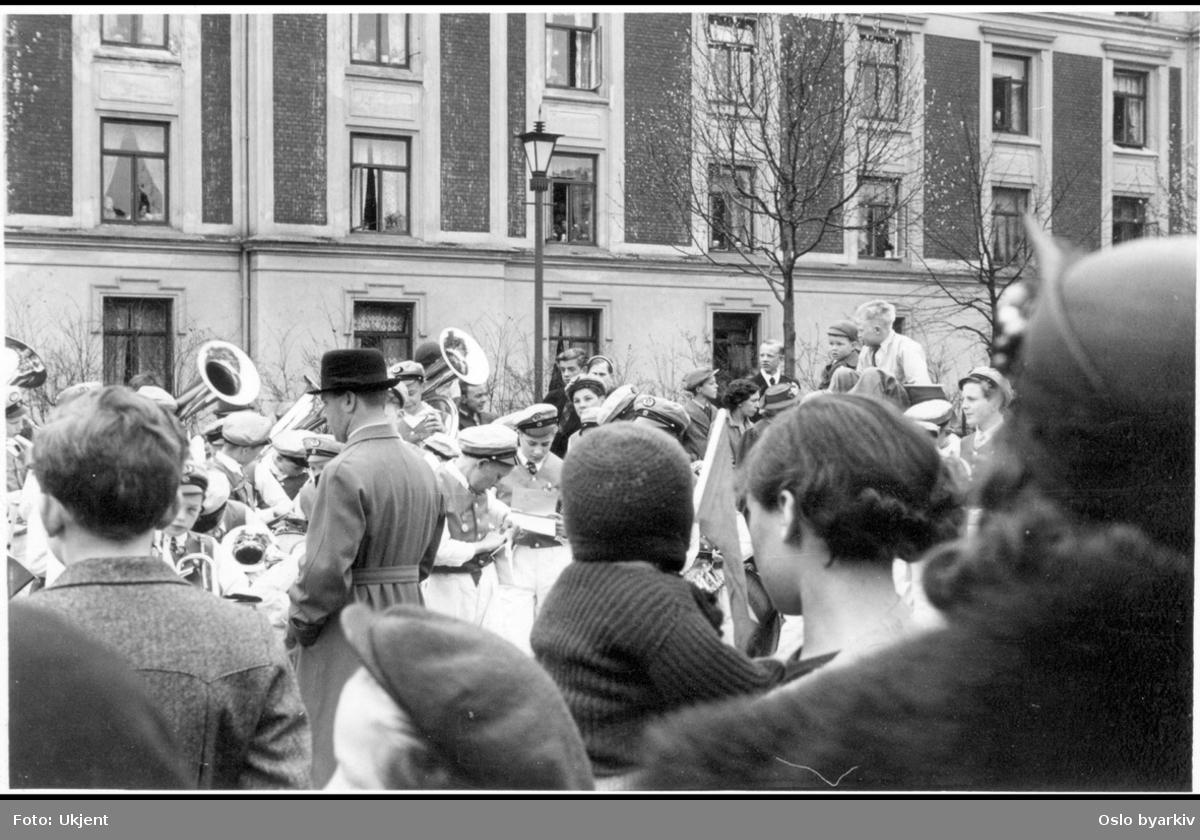 Guttemusikanter med tilhørere i gata.