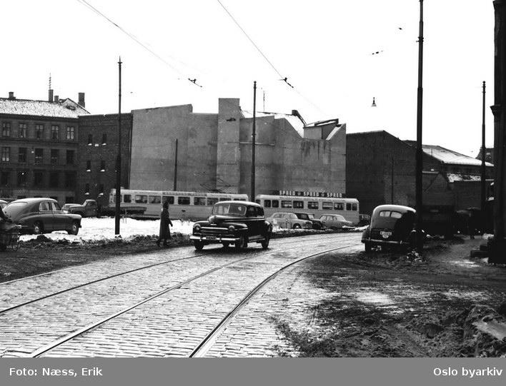 Oslo Sporveier. Trikk motorvogn og tilhenger type Høka MBO og TBO på linje 4, Kjelsås-Bergkrystallen, på vei inn i Schweigaards gate fra Vognmannsgata. Lastebil, privatbiler. Gammel Vaterlandbebyggelse. Trikkespor i Vognmannsgata.