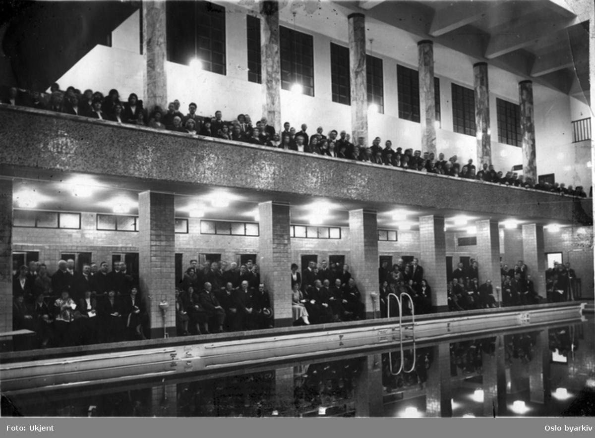 Innviterte gjester under åpningsseremonien av svømmehallen i det nye Torggata bad. Sittende og stående langs bassenget i svømmehallen og oppe langs galleriet i andre etasje. Marmorsøyler. Galleriet dekorert med fargede moaikkfliser. Fargede fliser i Svømmehall. Svømmehallen tatt i bruk 1. desember 1931.