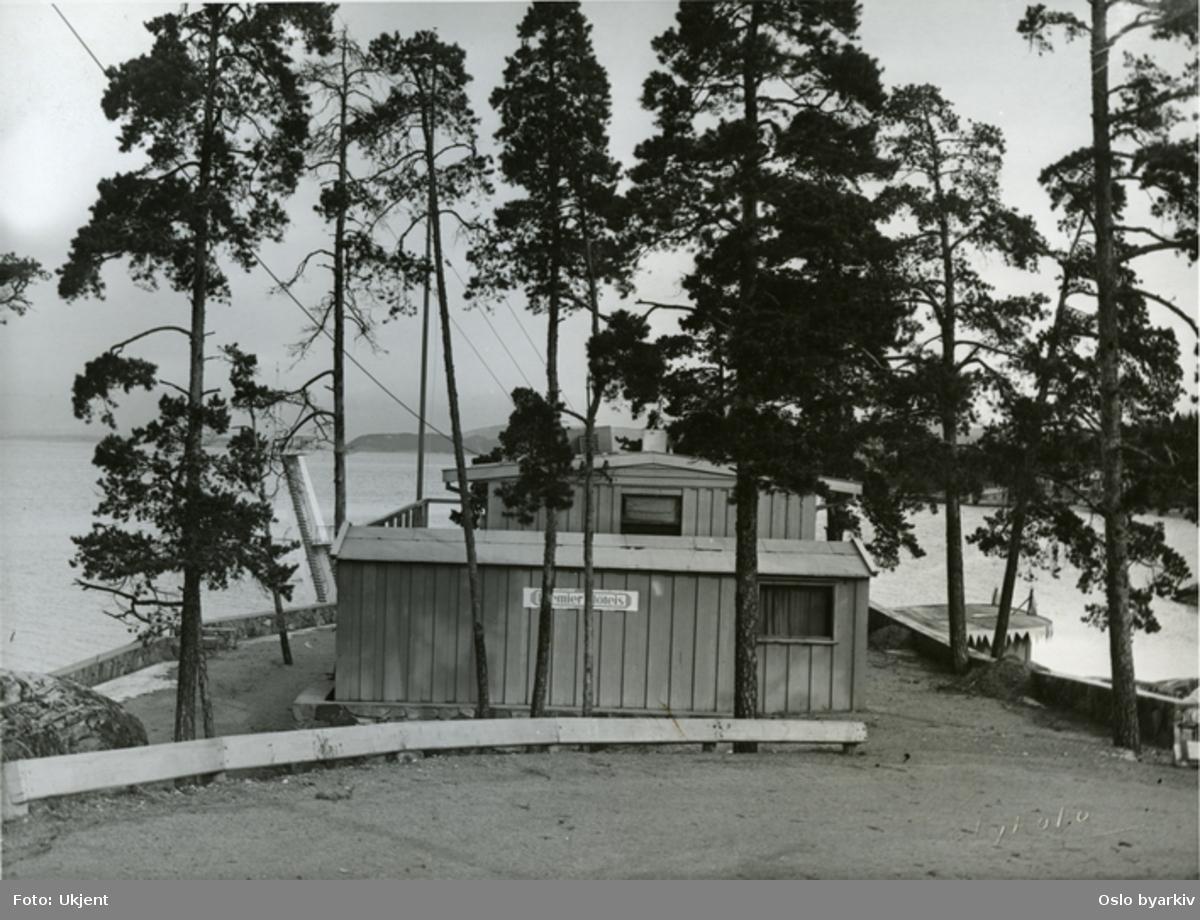 Ingierstrand bad. Foruten hovedresturanten med sine terrasser for friluftservering, så inngikk det i driften en mindre utesevering nede ved stranden. Reklame for Premier fløteis på veggen. Til venstre mellom trærne ses stupetårnet.