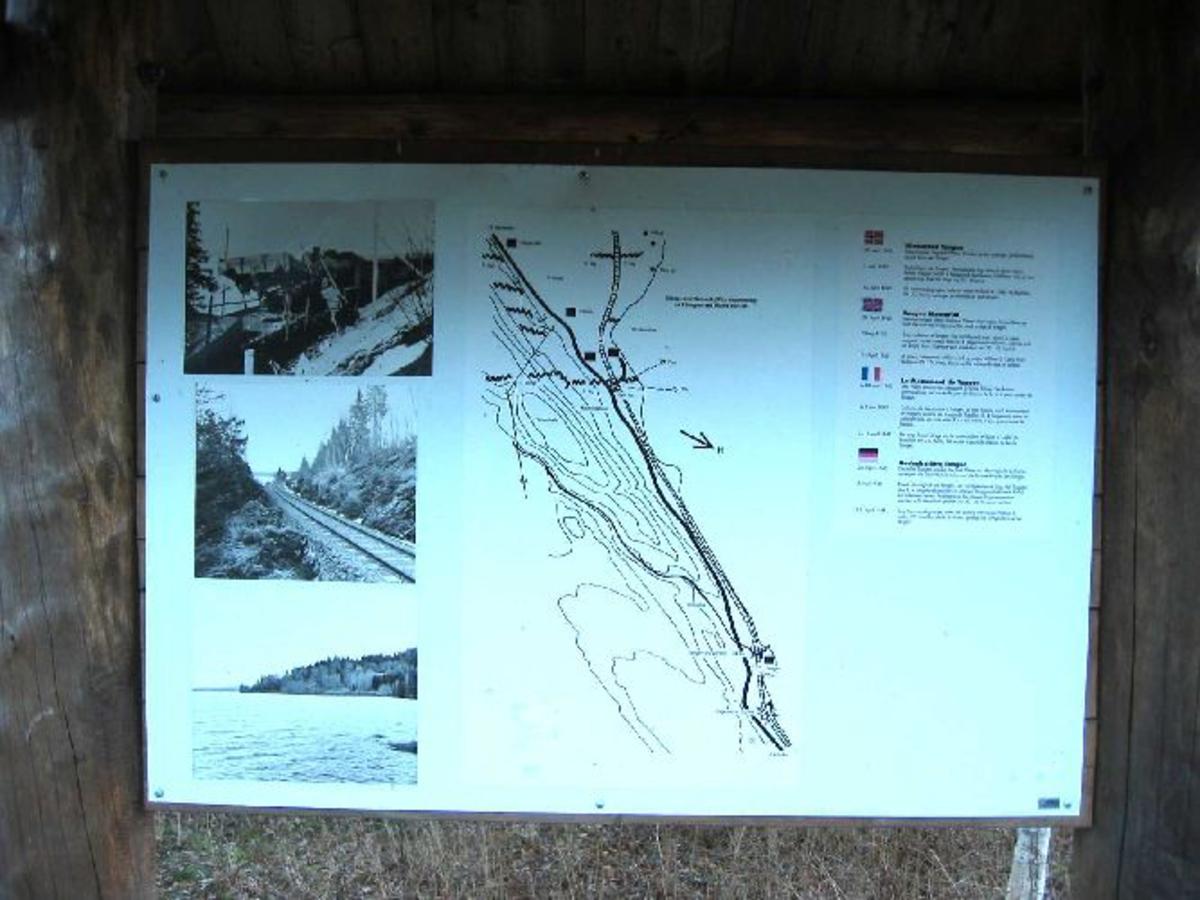 Informasjonstavle på norsk, engelsk tysk og fransk om hendelsene på dette stedet i 1940 og 1945.