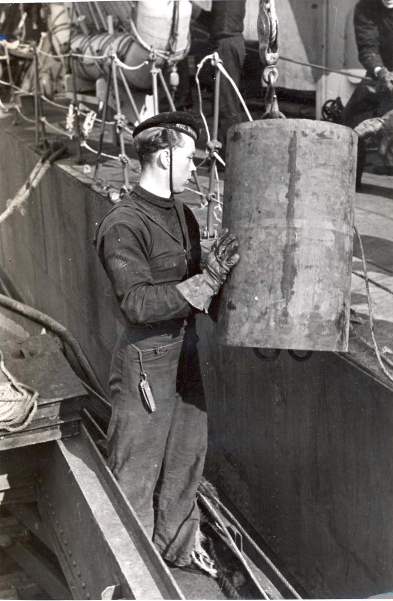 """Enkeltbilde. Jageren """"Stord"""" under oppøving, klarsjøing. Dypvannsminer blir lastet ombord under oppholdet i Scapa Flow."""