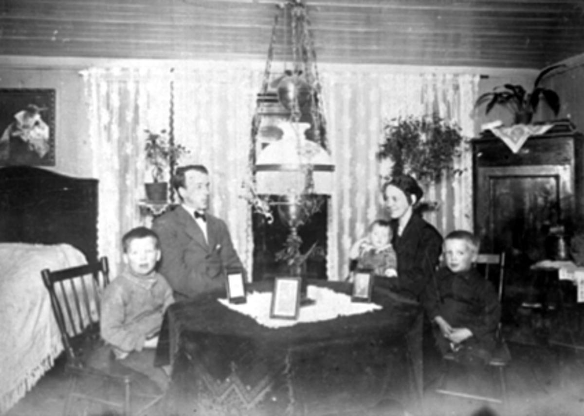 Interiør stue, familien Arnesen, seng, hjørneskap, parafinlampe. Fra v: Arvid, Adolf, Gudrun, Ingrid og Gunnar Arnesen. Adolf og Gudrun Arnesen var sterkt engasjert innen Arbeider-partiet. Var også med på høstrevyene i Hamar Park.