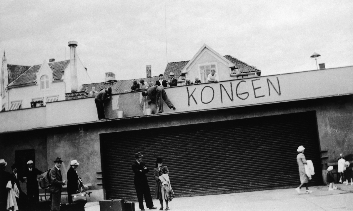 ØSTRE TORG MED RUTEBILTAKET, FJERNER PÅSKRIFTEN : LEVE KONGEN, UNDER KRIGEN, BUSSTASJONEN.